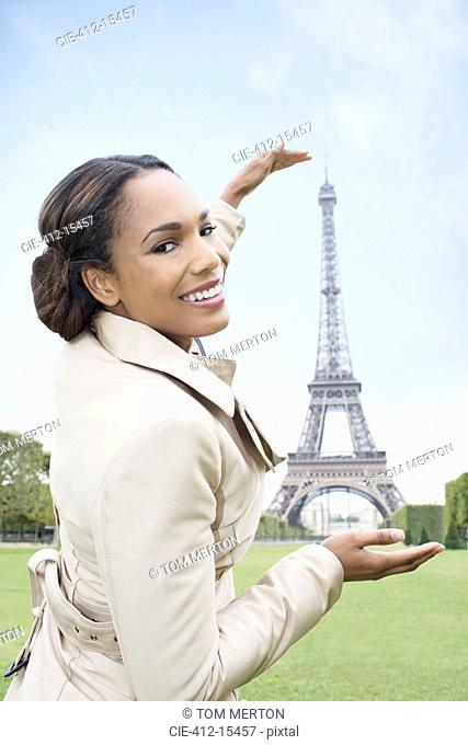 Woman posing as if to hold Eiffel Tower, Paris, France