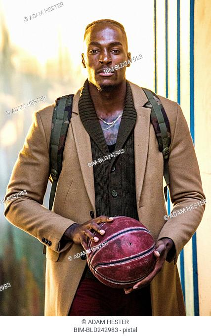 Black man wearing backpack holding basketball