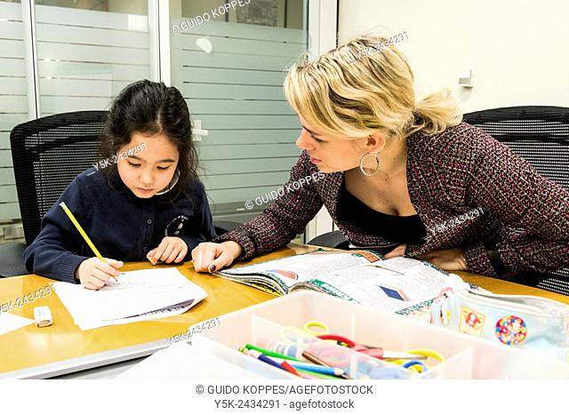 New York, USA. Female teacher at 't Klokhuis, a school for Dutch language and culture, teaching a young student Dutch idiom