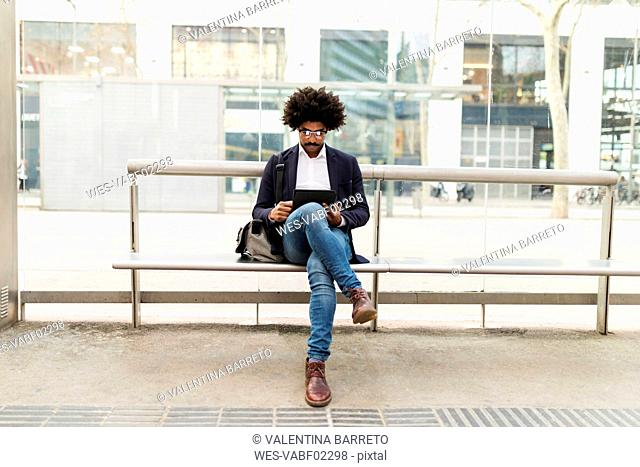 Spain, Barcelona, businessman in the city sitting on bench at a station using tablet