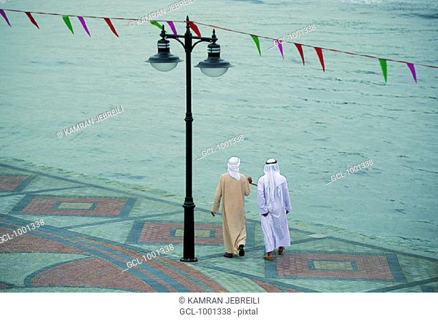 Two Arab men going for a walk at the creek in Dubai, UAE