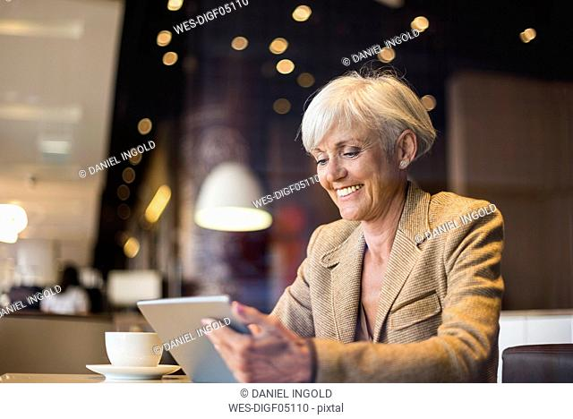 Smiling senior businesswoman using tablet in a cafe