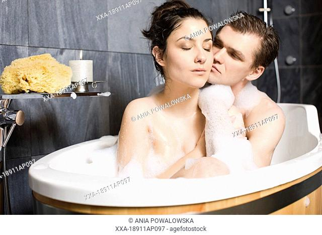 Couple embracing in bathtub