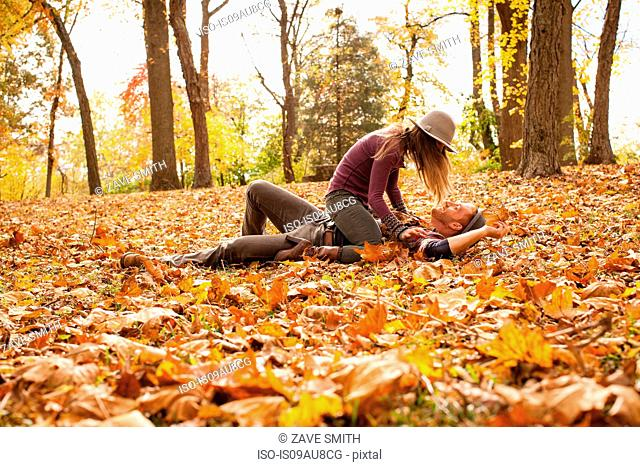 Young couple play fighting on autumn forest floor