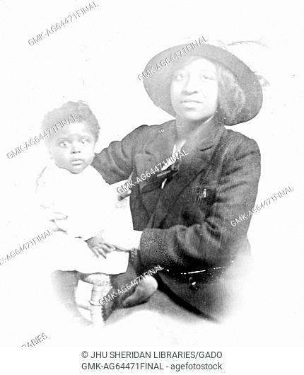 African-American mother wearing a hat and holding her daughter, who has a surprised facial expression, 1944