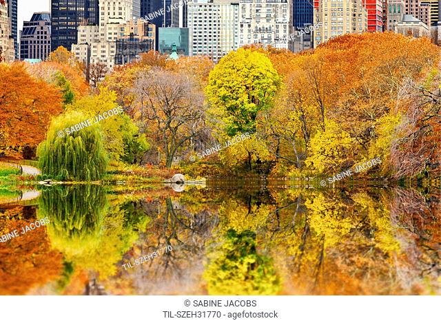 Overlooking The Pond in Central Park, Manhattan, New York City, on an autumn day. View towards Central Park South buildings with colorful autumn trees in the...