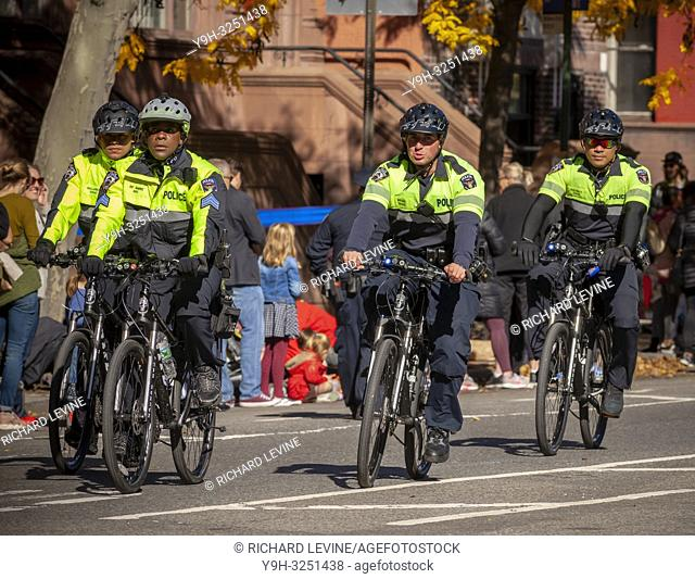 NYPD officers mounted on bicycles pass through Harlem in New York near the 22 mile mark near Mount Morris Park on Sunday, November 4