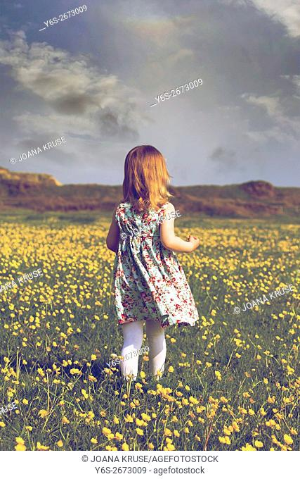 a 3 year old girl running through a flower meadow