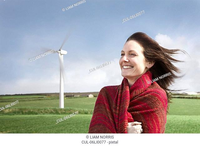 Woman with hair blowing on a wind farm