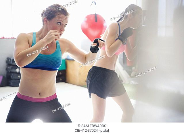 Determined female boxers shadowboxing in gym