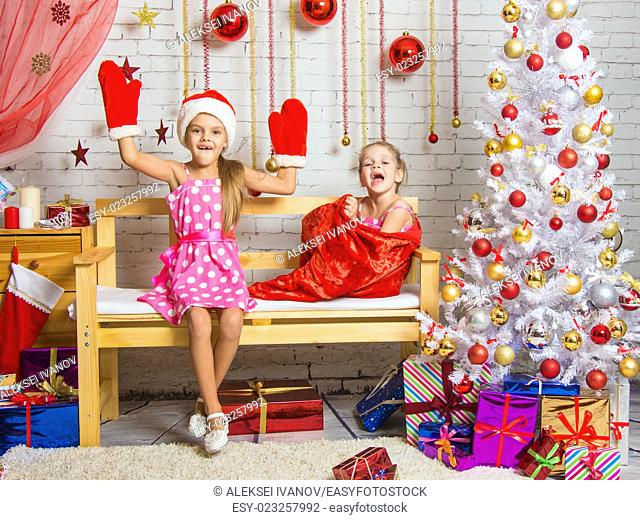 Two funny sisters four girls and six years of playing and having fun in the home New Years interior
