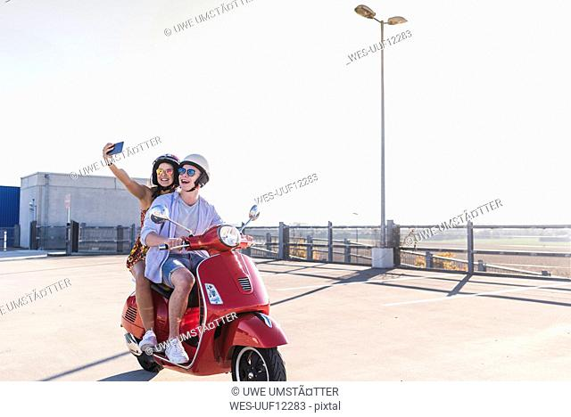 Happy young couple taking a selfie on motor scooter on parking level