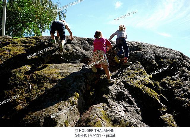 Schweden, Insel Grinda, Kinder klettern auf einen Felsen