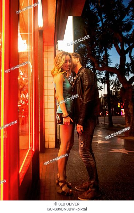 Romantic young couple by shop front with neon sign at night