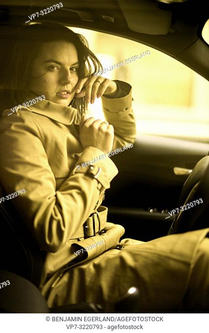 portrait of playful woman sitting in car at driver's side, wearing coat, sensual flirtatious emotion, in Munich, Germany