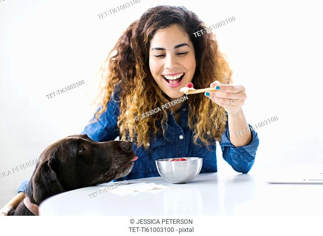 Woman with dog eating snack