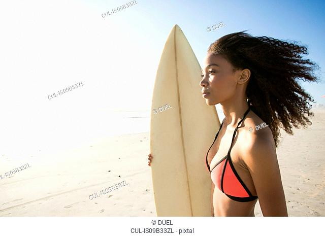Beautiful young female surfer gazing out from beach, Cape Town, Western Cape, South Africa