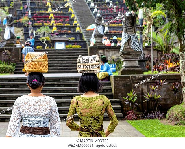 Indonesia, Women carrying basket on head and walking at Pura Penataran Agung temple
