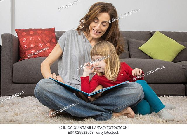 blonde child three years old, with red and green clothes, leaning on mother woman in jeans, reading together a story tale book, sitting on carpet indoor home