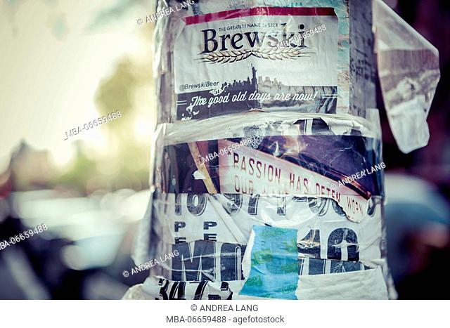 Ads and stickers on a lamp post, streetview, Manhatten, New York, USA