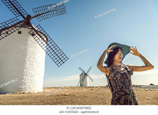 A young Chinese woman standing beside the famous windmills in Campo Criptana, where the stories of Don Quixote come from; Ciudad Real, Castile-La Mancha, Spain