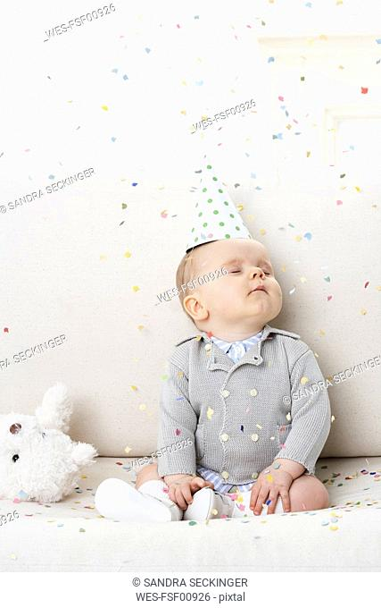 Portrait of baby boy with eyes closed wearing paper hat