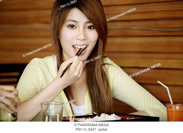 Portrait of a young woman eating food with chopsticks