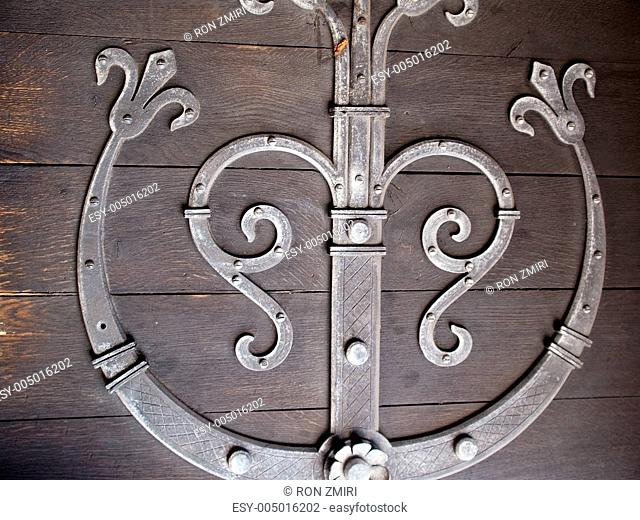 Detailes of an old wooden door with metal decoration