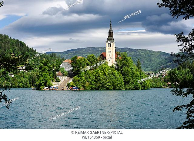 Bled Island in Spring with stairs to Catholic pilgrimage church of the Assumption of Mary with Pletna boats in turquoise Lake Bled Slovenia