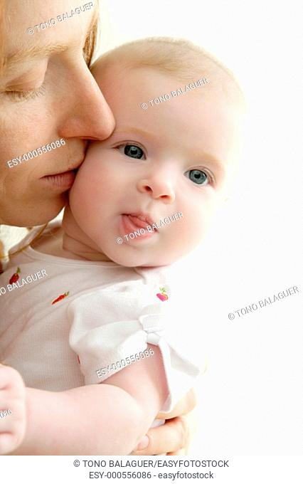 mother kissing little baby smiling on white background
