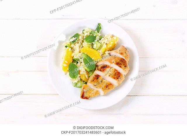 roasted chicken breast with rice and oranges on white plate