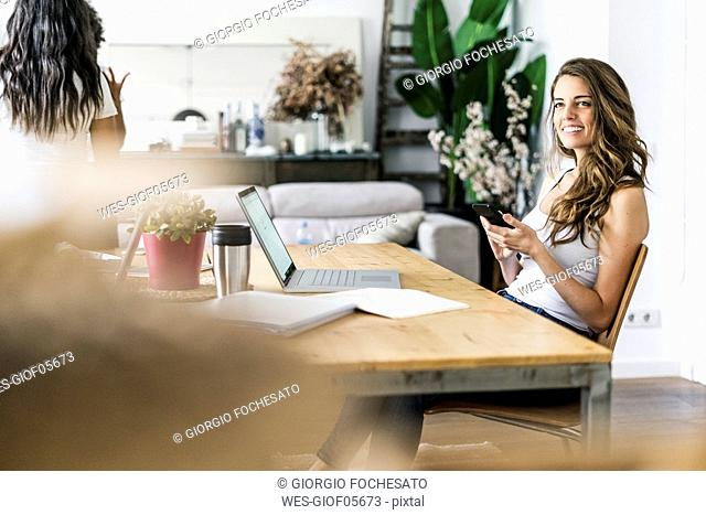 Smiling woman with cell phone at table at home