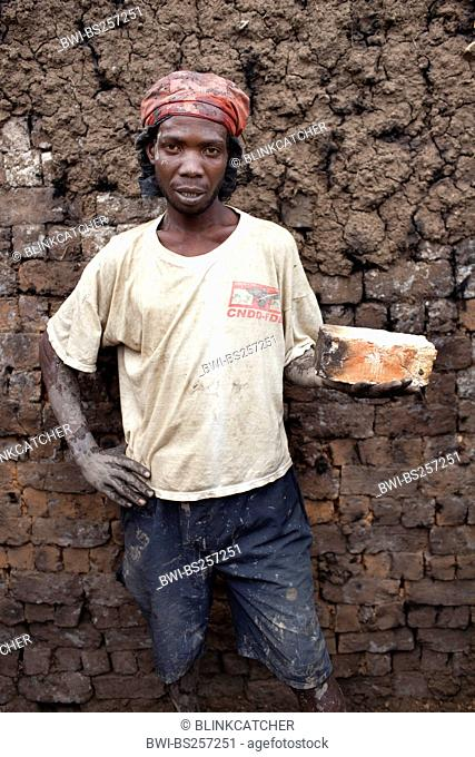 portrait of a worker in a brickery holding one of the bricks in hand which are formed of mud on location and burned in a traditional furnace