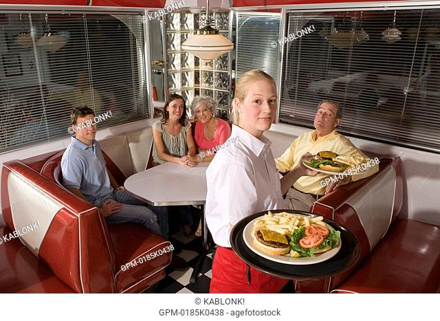 Portrait of waitress serving young couple and senior couple in old-fashioned diner, high angle view
