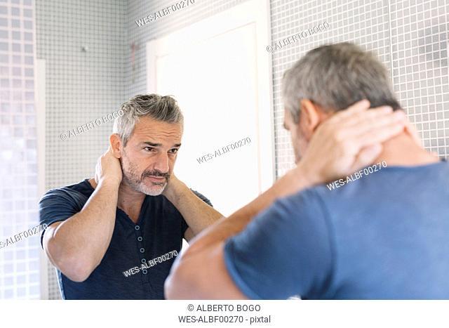 Mature man looking in bathroom mirror