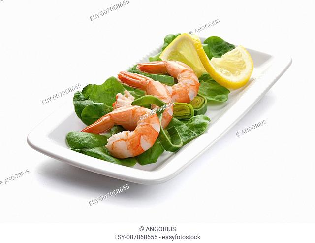 Three shrimp's tails with leek, lettuce and lemon on the white plate