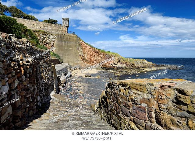 Rock wall path to beach at Crail in Fife Scotland UK with lookout tower turret of Crail House over the North Sea