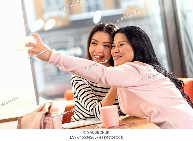 And now smile. Delighted positive young women hugging each other and looking into the smartphone camera while taking selfies