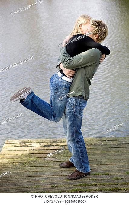 Man lifting woman on a wooden dock