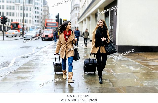 UK, London, Two friends exploring the city, arriving with trolley bags