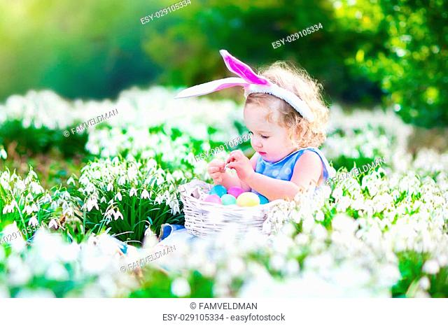 Adorable curly toddler girl wearing bunny ears playing with Easter eggs in a white basket sitting in a sunny garden with first white spring flowers