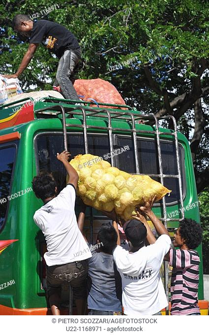 Dili (East Timor): some man lifting a cabbage's bag on a mikrolet (Indonesian-style minibus) roof at the bus station in the Leicidere neighborhood