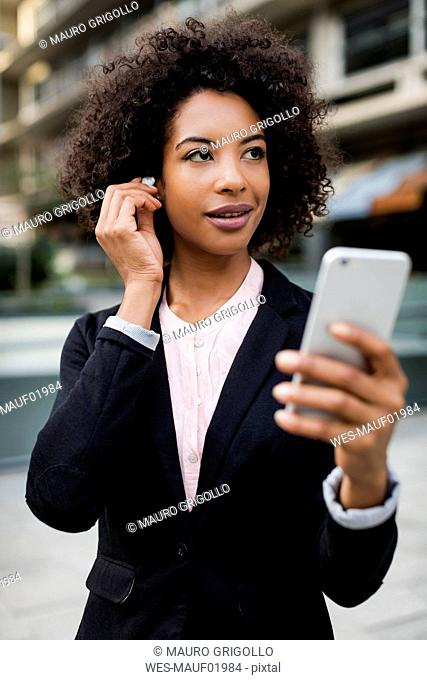 Portrait of smiling usinesswoman with smartphone putting on earphones
