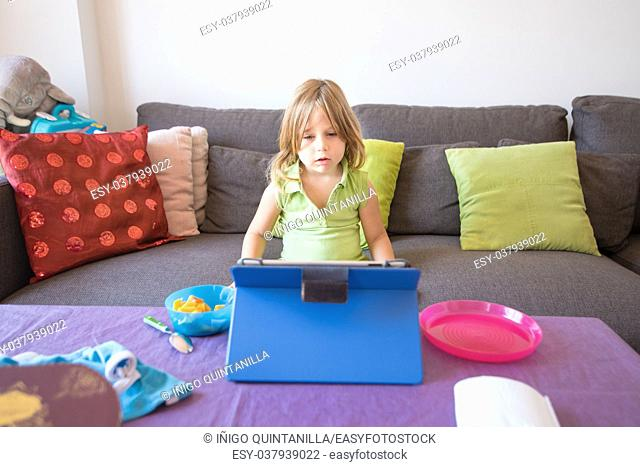 four years old blonde child with green sleeveless shirt sitting on brown sofa, watching digital tablet on table