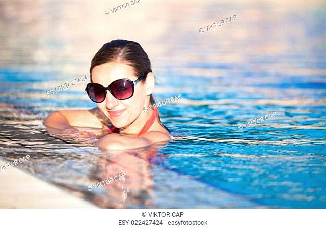 Portrait of a young woman relaxing in a swimming pool