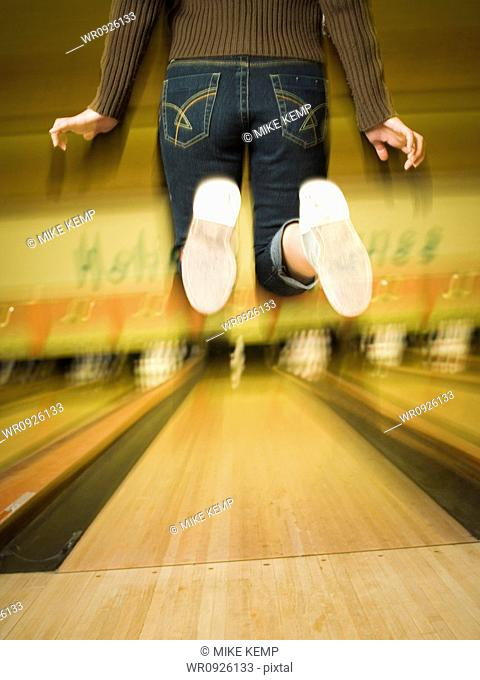 Rear view of a teenage girl jumping in a bowling alley