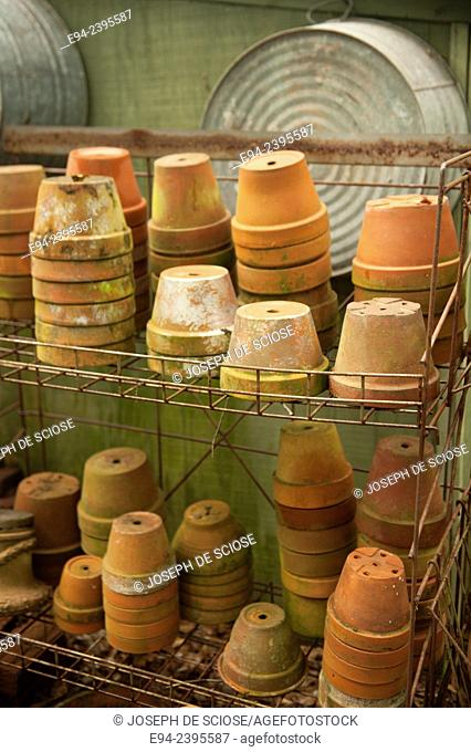 A stack of terra cotta pots on shelves in a garden. Georgia USA