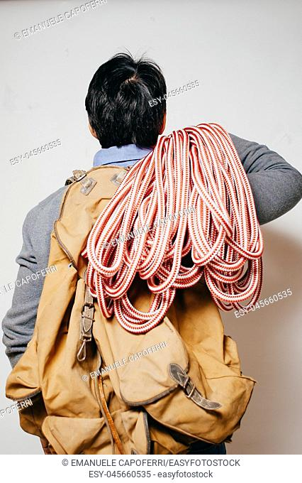 man with backpack and mountain rope, casual dressed, seen from behind, white background