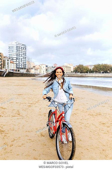 Spain, Gijon, young woman riding a bike on the beach