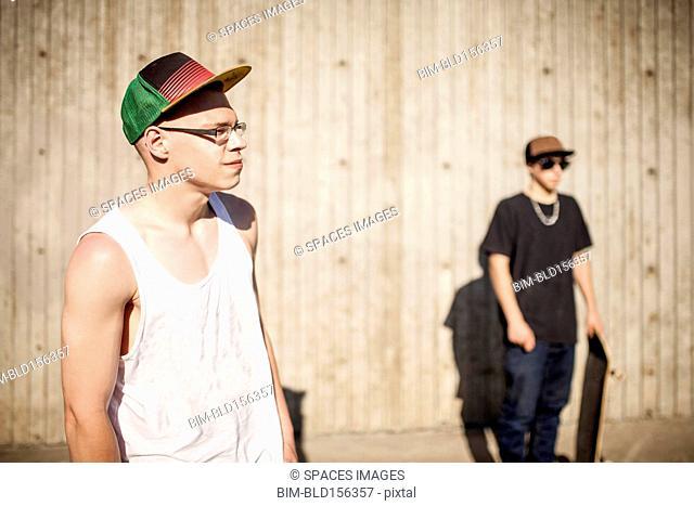Caucasian men with skateboards near wooden wall
